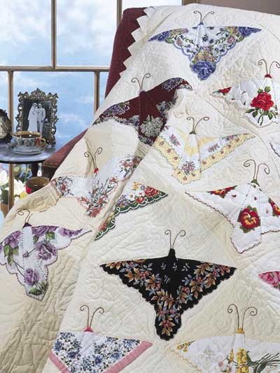 Vintage hankies placed to look like butterflies on a white quilt with the feelers embroidered in black. #vintage #hankies #quilt